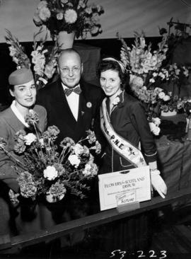 Miss P.N.E., model dressed as stewardess, and dignitary with Flowers by Air exhibit in horticultu...