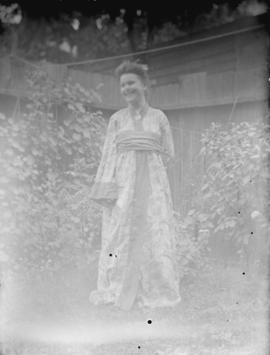[Woman in print dress standing in front of a fence]