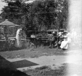 [Woman taking a photograph of children at a picnic table]