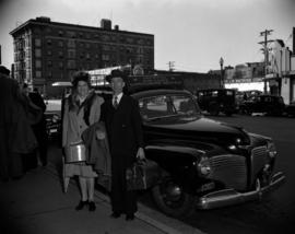 [Couple standing beside a Vancouver Air Lines Limousine Service car]