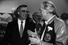 Unidentified man and Norman Young talking indoors at Centennial birthday party