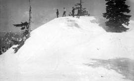 [Four men at the top of a snowy slope]