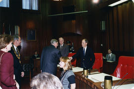 Roméo LeBlanc shaking hands with Gordon Price in council chambers, Donald Bellamy in background