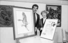 Unidentified man and May Brown holding prints from the Centennial gift program