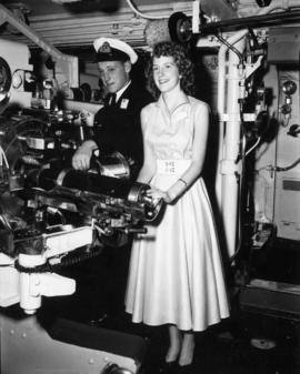 Miss P.N.E. contestant with officer in the engine room of the H.M.S. Sheffield