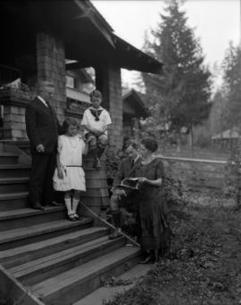 Mr. Pooley and family [on steps of house in Dollarton]