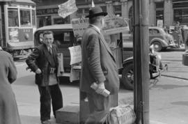 [Newspaper vendor near the corner of Granville Street and Robson Street]