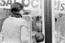 Woman and child at front window of Oceanic Cost Plus Imports