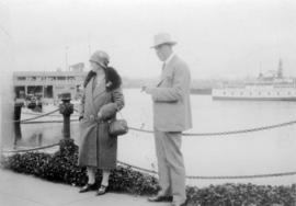 [L.D. Taylor and unidentified woman standing near dock, with ships in background]