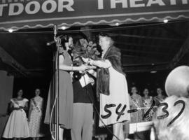 Nancy Hansen receiving roses on Outdoor Theatre stage after being named Miss P.N.E. 1954