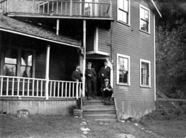 [James Crookall and others on the porch of a house]