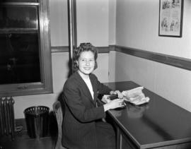 [B.C. Telephone employee working at a desk]