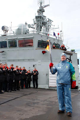 Torchbearer 290 Brett Rickard carries the flame on the HMCS Vancouver in British Columbia