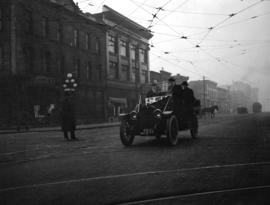 [Men in a taxicab on Granville Street at Davie Street]