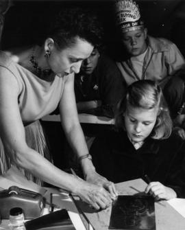 Woman and girl working on copper craft at 1957 P.N.E. Hobby Show