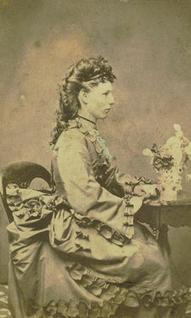 [Studio portrait of woman, seated, showing profile]