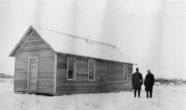 Two men standing by a cabin in the snow