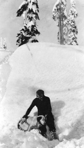 [Man and dog in front of shack buried by snow on Grouse Mountain]
