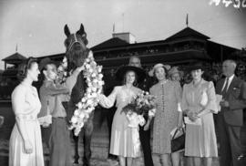 [Miss. Anna Neagle and others at Hastings Park racetrack standing with winning horse and jockey]