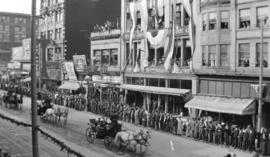 [A parade of horse-drawn carriages on the north side of the Unit Block of West Hastings Street fo...