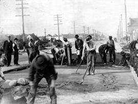 [Men doing road work on] Main St. - placing cushion
