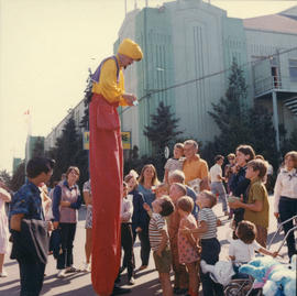 Performer on stilts with children on P.N.E. grounds