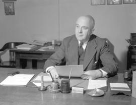 Mr. Wilkinson [seated at a desk]