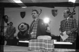 Unidentified man and Mike Harcourt stand behind the haggis