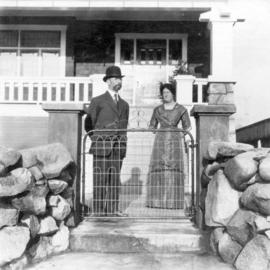 [An unidentified couple in front of a house]
