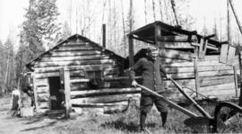[Man and woman working field near log house]