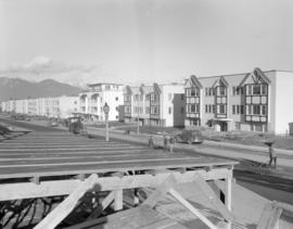 [Apartment buildings along Oak or Cambie at W. 24th Avenue with road work being completed in front]