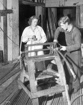 [Woman assisting man to make steel cables]