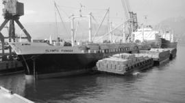 M.S. Olympic Pioneer [at dock, with lumber-filled barges alongside]