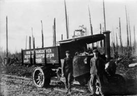 [Two unidentified men standing in front of steam truck with lettering 'North Vancouver Distr...