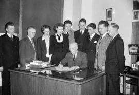 [Group gathered around a desk while a man signs a recruitement poster]