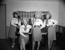 [Women in cowgirl costumes at a piano for a CBC radio broadcast]