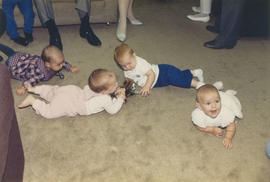 Babies born on April 6 playing on carpeted floor
