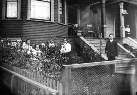 Family in garden in front of urban house