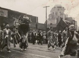 Lion dancers and other people marching in the V-J Day parade on Powell Street
