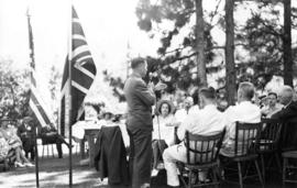 Man speaking to picnic attendees in front of American and British flags