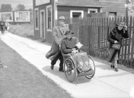 [A man pushing a woman in a wheelchair to see King George VI and Queen Elizabeth]