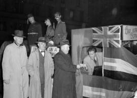 [Men lining up to buy Victory Bonds from a parade float depicting  Mussolini, Hitler, and Hiro Hito]