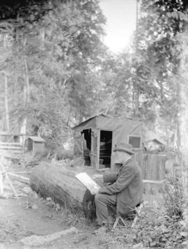 [A.A. Bradbury sketching in forest at his camp at the foot of Alma Street]