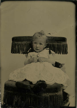 Portrait of infant Laura, on fringe-backed chair