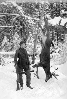 [Teenage boy standing next to deer strung from tree branch in snow covered forest]