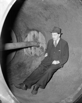 [Man sitting inside a large pipe]
