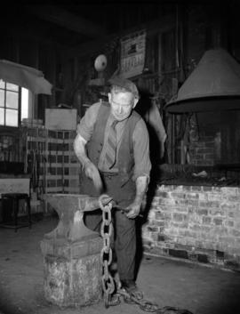 [Blacksmith hammering a chain link on an anvil]