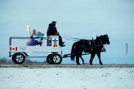 Day 74 Torchbearer 85 Rose Fleury carries the flame on a horse carriage in Duck Lake, Saskatchewan