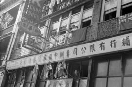 [People waving flags out of windows in Chinatown during VJ Day celebrations]