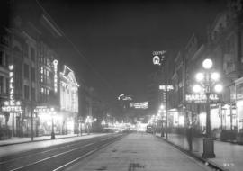 [View of illuminated signs on Hastings Street, looking east from Abbott Street]